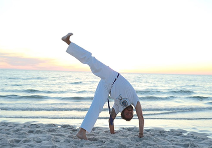 image of man doing a capoeira pose on the beach at sunset
