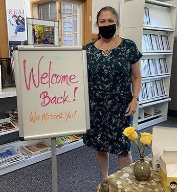 """Image of Library Director Tricia Ford with a """"Welcome Back (Inside)!"""" signT"""